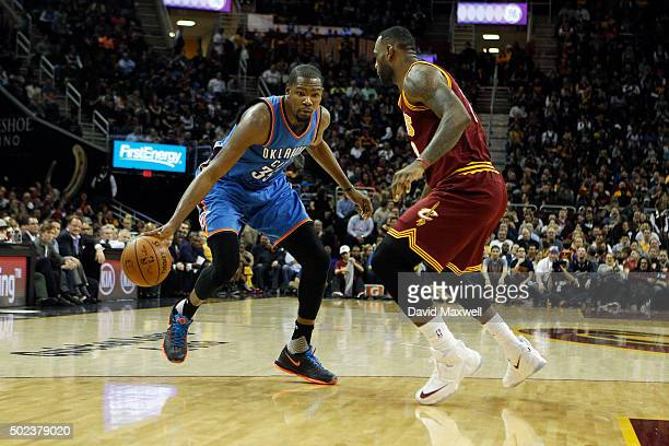 LeBron James of the Cleveland Cavaliers defends against Kevin Durant of the Oklahoma City Thunder during the first half of their game on December 17...