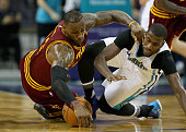 LeBron James of the Cleveland Cavaliers dives for a loose ball against Michael KiddGilchrist of the Charlotte Hornets during their game at Time...