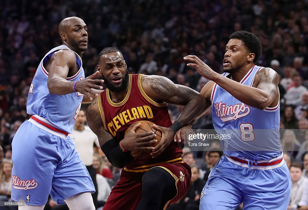 LeBron James #23 of the Cleveland Cavaliers dribbles between Rudy Gay #8 and Anthony Tolliver #43 of the Sacramento Kings at Golden 1 Center on January 13, 2017 in Sacramento, California.