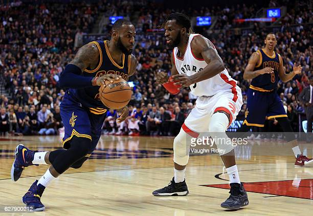 Lebron James of the Cleveland Cavaliers dribbles the ball as DeMarre Carroll of the Toronto Raptors defends during the first half of an NBA game at...