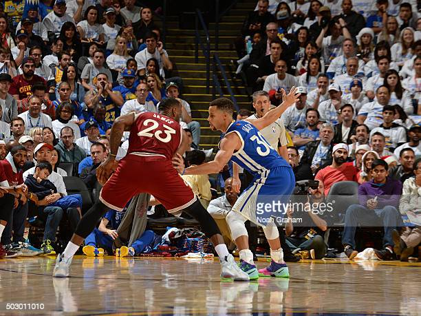LeBron James of the Cleveland Cavaliers dribbles the ball while defended by Stephen Curry of the Golden State Warriors on December 25 2015 at ORACLE...