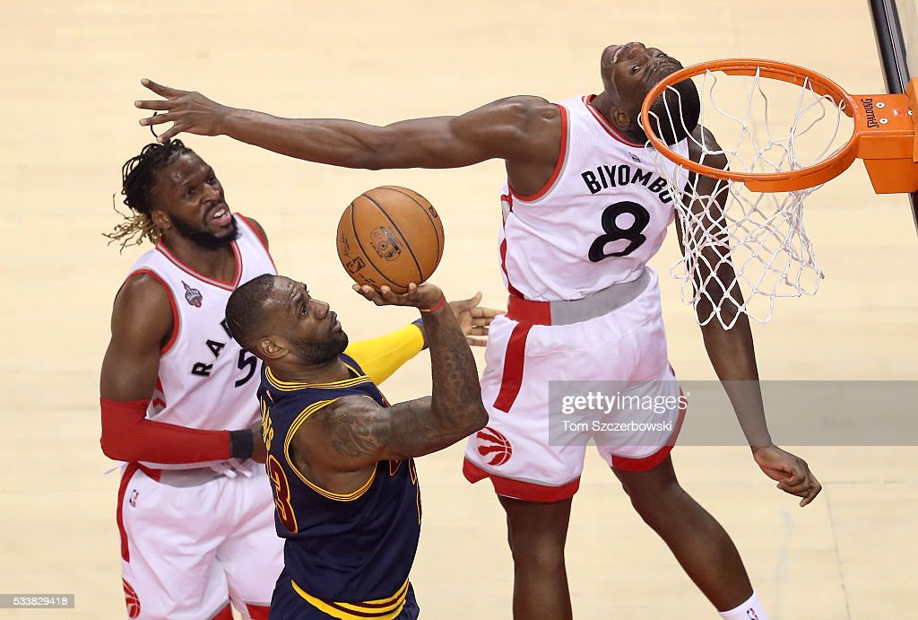 LeBron James of the Cleveland Cavaliers drives to the basket against Bismack Biyombo and DeMarre Carroll of the Toronto Raptors in the first half in...