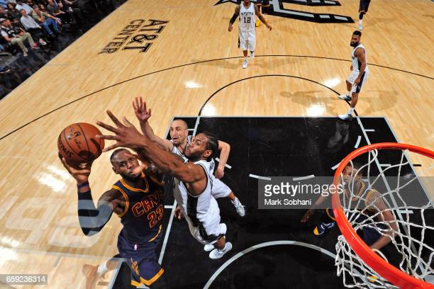 LeBron James of the Cleveland Cavaliers drives to the basket around Manu Ginobili and Kawhi Leonard of the San Antonio Spurs during the game on March...