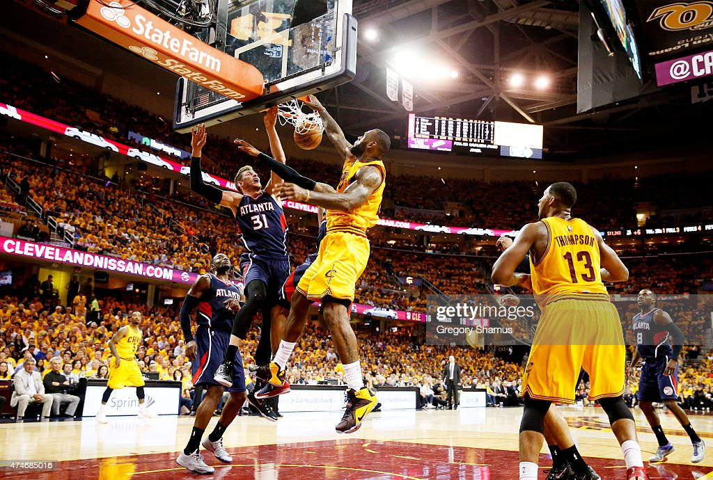 <a gi-track='captionPersonalityLinkClicked' href=/galleries/search?phrase=LeBron+James&family=editorial&specificpeople=201474 ng-click='$event.stopPropagation()'>LeBron James</a> #23 of the Cleveland Cavaliers dunks against <a gi-track='captionPersonalityLinkClicked' href=/galleries/search?phrase=Mike+Muscala&family=editorial&specificpeople=7563430 ng-click='$event.stopPropagation()'>Mike Muscala</a> #31 and <a gi-track='captionPersonalityLinkClicked' href=/galleries/search?phrase=Kent+Bazemore&family=editorial&specificpeople=6846101 ng-click='$event.stopPropagation()'>Kent Bazemore</a> #24 of the Atlanta Hawks in the third quarter during Game Three of the Eastern Conference Finals of the 2015 NBA Playoffs at Quicken Loans Arena on May 24, 2015 in Cleveland, Ohio.