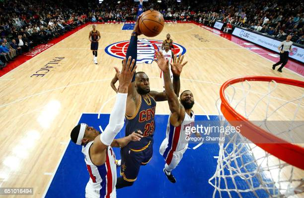 LeBron James of the Cleveland Cavaliers dunks between Marcus Morris and Tobias Harris of the Detroit Pistons during the second half at the Palace of...