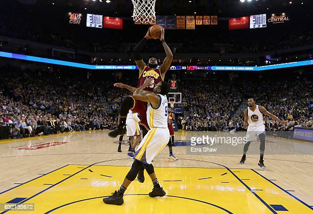 LeBron James of the Cleveland Cavaliers dunks over Andre Iguodala of the Golden State Warriors at ORACLE Arena on January 16 2017 in Oakland...