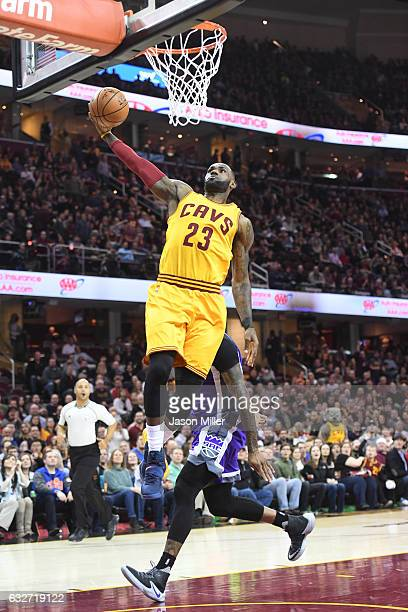 LeBron James of the Cleveland Cavaliers dunks over DeMarcus Cousins of the Sacramento Kings dunks during the first half at Quicken Loans Arena on...