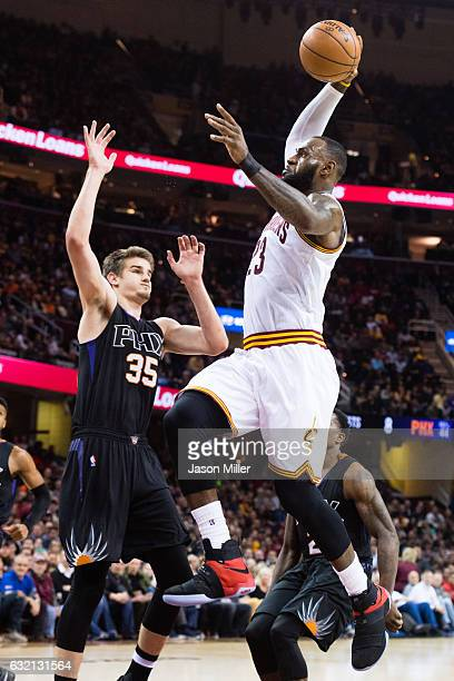 LeBron James of the Cleveland Cavaliers dunks over Dragan Bender of the Phoenix Suns during the first half against the Phoenix Suns at Quicken Loans...