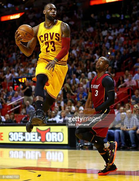 LeBron James of the Cleveland Cavaliers dunks over Dwyane Wade of the Miami Heat during a game at American Airlines Arena on March 19 2016 in Miami...