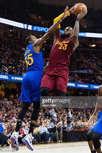 LeBron James of the Cleveland Cavaliers dunks over Kevin Durant of the Golden State Warriors during the second half at Quicken Loans Arena on...