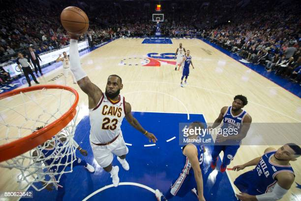 LeBron James of the Cleveland Cavaliers dunks the ball past Robert Covington Dario Saric Joel Embiid and Ben Simmons of the Philadelphia 76ers in the...