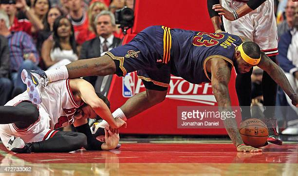 LeBron James of the Cleveland Cavaliers falls over Nikola Mirotic of the Chicago Bulls in Game Three of the Eastern Conference Semifinals of the 2015...