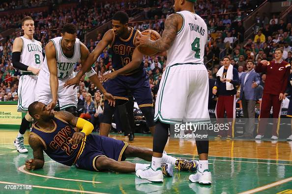 LeBron James of the Cleveland Cavaliers falls to the ground after a flagrant foul by Evan Turner of the Boston Celtics during the second quarter in...