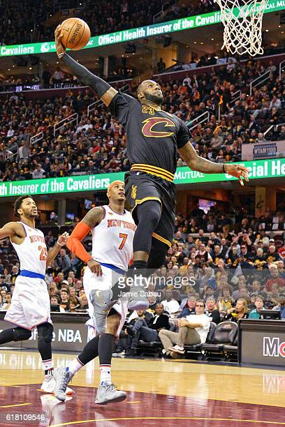 LeBron James of the Cleveland Cavaliers finishes off a fast break with a dunk in the third quarter as Carmelo Anthony of the New York Knicks watches...