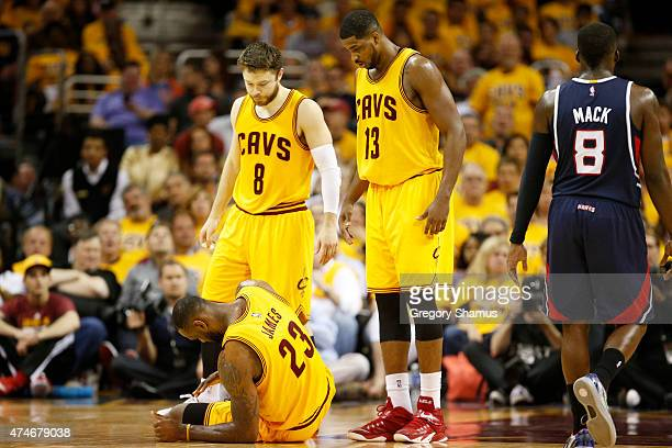 LeBron James of the Cleveland Cavaliers gets up from the court as Matthew Dellavedova and Tristan Thompson look on in the third quarter against the...