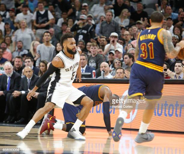 LeBron James of the Cleveland Cavaliers goes down on the court as play continuous with Patty Mills of the San Antonio Spurs guarding Deron Williams...
