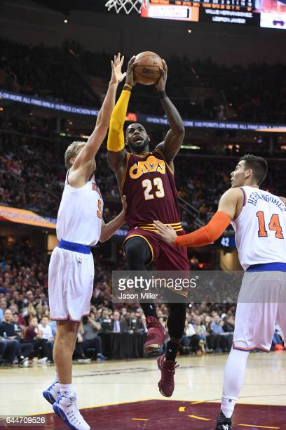 LeBron James of the Cleveland Cavaliers goes up for a shot between Mindaugas Kuzminskas and Willy Hernangomez of the New York Knicks during the...