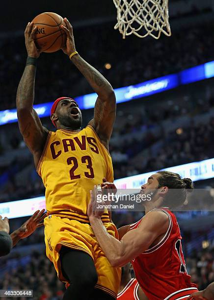 LeBron James of the Cleveland Cavaliers goes up for a shot over Joakim Noah of the Chicago Bulls at United Center on February 12 2015 in Chicago...
