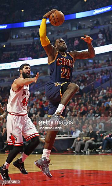 LeBron James of the Cleveland Cavaliers goes up for a shot past Nikola Mirotic of the Chicago Bulls during the season opening game at the United...