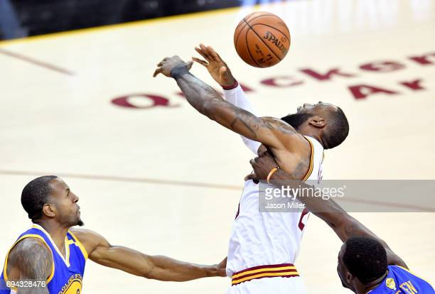 LeBron James of the Cleveland Cavaliers goes up with the ball against Andre Iguodala and Draymond Green of the Golden State Warriors in the first...