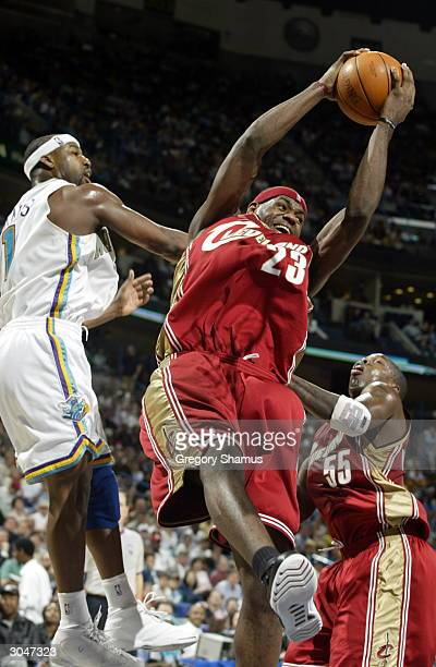LeBron James of the Cleveland Cavaliers grabs a rebound against Baron Davis of the New Orleans Hornets on March 5 2004 in New Orleans Louisiana NOTE...