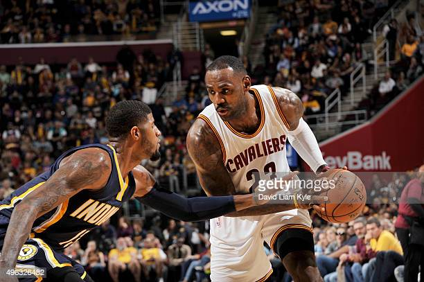 LeBron James of the Cleveland Cavaliers handles the ball against Paul George of the Indiana Pacers on November 8 2015 at Quicken Loans Arena in...