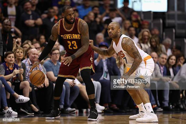 LeBron James of the Cleveland Cavaliers handles the ball against PJ Tucker of the Phoenix Suns during the first half of the NBA game at Talking Stick...