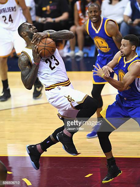 LeBron James of the Cleveland Cavaliers handles the ball as Stephen Curry of the Golden State Warriors reacts during the first half in Game 4 of the...