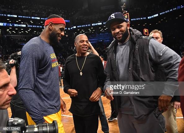 LeBron James of the Cleveland Cavaliers Hip Hop Artist JayZ and CC Sabathia of the New York Yankees chats after the game against the Brooklyn Nets at...