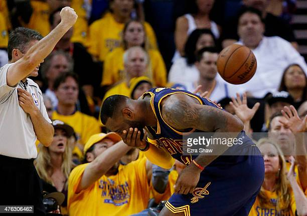 LeBron James of the Cleveland Cavaliers holds his face after being fouled by Draymond Green of the Golden State Warriors in the fourth quarter during...
