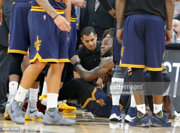 LeBron James of the Cleveland Cavaliers is attended to by trainers after he went down during game against the San Antonio Spurs at ATT Center on...