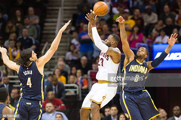 LeBron James of the Cleveland Cavaliers is blocked by CJ Miles while under pressure from Luis Scola of the Indiana Pacers during the second half at...