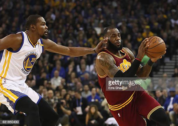LeBron James of the Cleveland Cavaliers is guarded by Kevin Durant of the Golden State Warriors at ORACLE Arena on January 16 2017 in Oakland...