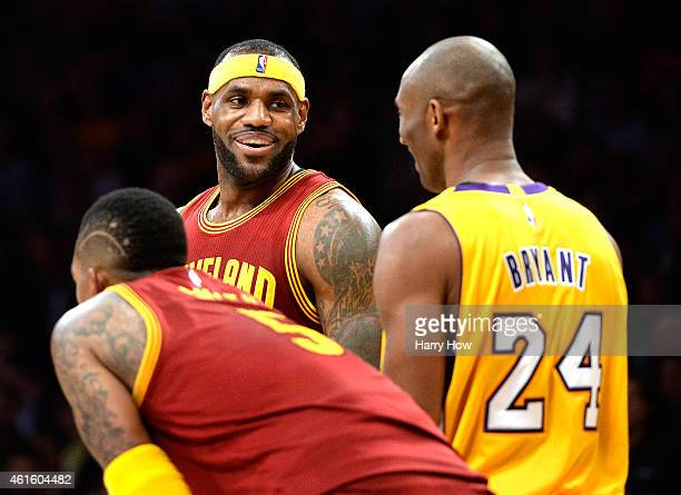 LeBron James of the Cleveland Cavaliers laughs with Kobe Bryant of the Los Angeles Lakers after a missed dunk in front of JR Smith during the first...