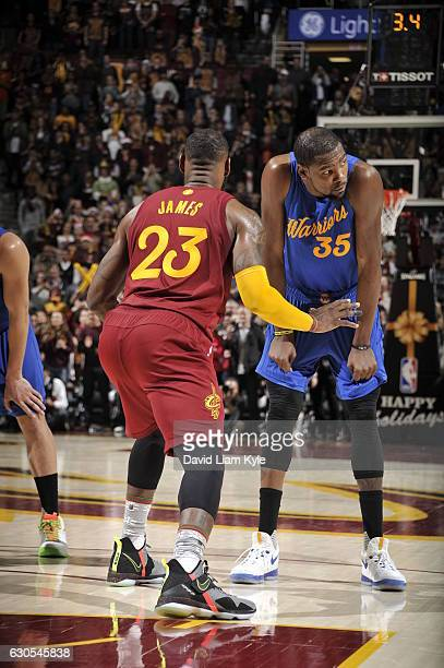 LeBron James of the Cleveland Cavaliers looks to defend Kevin Durant of the Golden State Warriors on December 25 2016 at Quicken Loans Arena in...