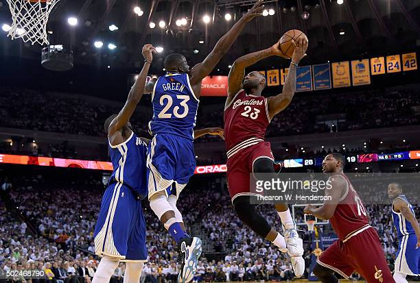 LeBron James of the Cleveland Cavaliers looks to get his shot off over Draymond Green of the Golden State Warriors during their NBA basketball game...