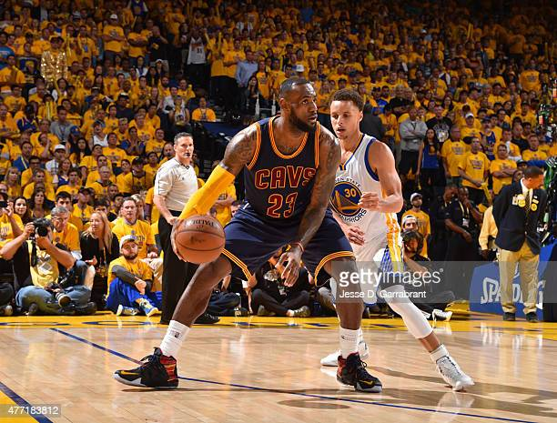 LeBron James of the Cleveland Cavaliers looks to pass the ball against Stephen Curry of the Golden State Warriors at the Oracle Arena During Game...
