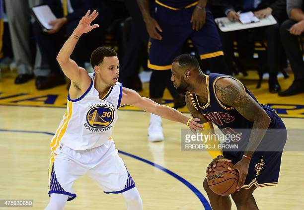 LeBron James of the Cleveland Cavaliers looks to pass under pressure from Stephen Curry of the Golden State Warriors late in Game 1 of the 2015 NBA...