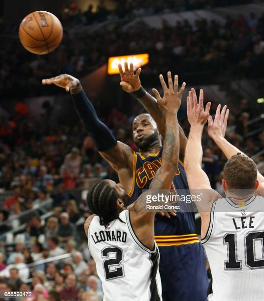 LeBron James of the Cleveland Cavaliers passes off in front of Kawhi Leonard of the San Antonio Spurs at ATT Center on March 27 2017 in San Antonio...