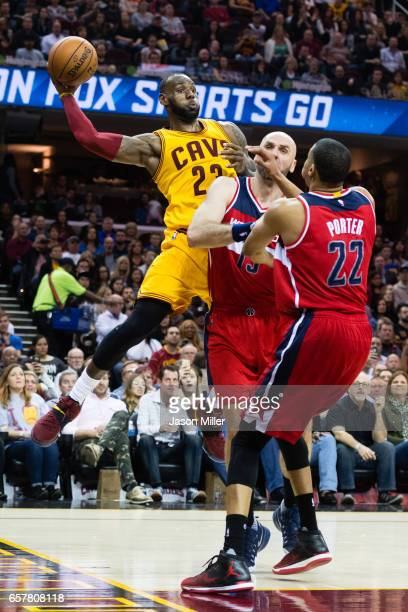 LeBron James of the Cleveland Cavaliers passes over Marcin Gortat and Otto Porter Jr #22 of the Washington Wizards during the second half at Quicken...