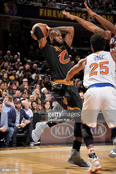 LeBron James of the Cleveland Cavaliers passes the ball around defenders of the New York Knicks on October 25 2016 at Quicken Loans Arena in...