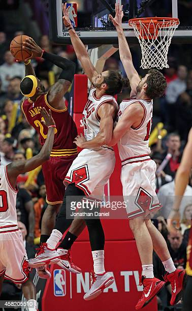 LeBron James of the Cleveland Cavaliers puts up a shot against Joakim Noah and Pau Gasol of the Chicago Bulls at the United Center on October 31 2014...