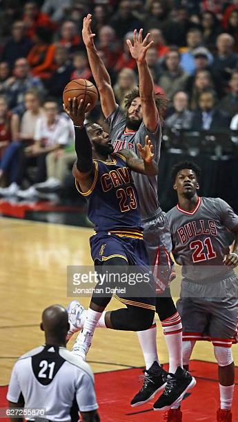 LeBron James of the Cleveland Cavaliers puts up a shot against Robin Lopez of the Chicago Bulls at the United Center on December 2 2016 in Chicago...