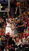 LeBron James of the Cleveland Cavaliers puts up a shot over Jimmy Buter and Taj Gibson of the Chicago Bulls in Game Four of the Eastern Conference...