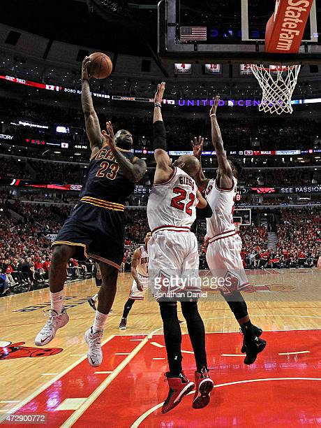 LeBron James of the Cleveland Cavaliers puts up a shot over Taj Gibson and Jimmy Butler of the Chicago Bulls in Game Four of the Eastern Conference...