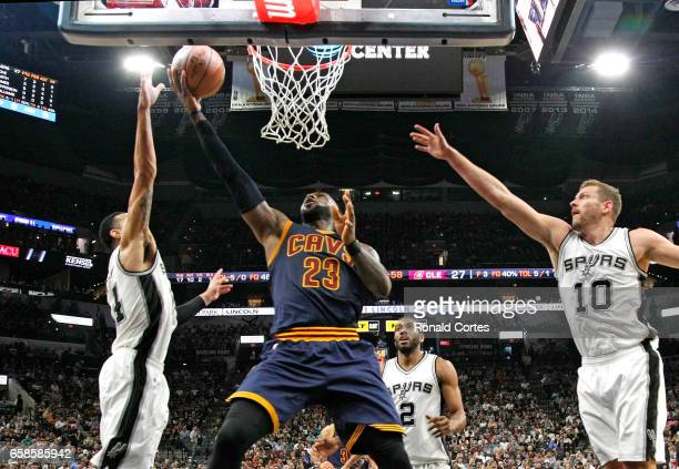 LeBron James of the Cleveland Cavaliers scores against Danny Green of the San Antonio Spurs and David Lee of the San Antonio Spurs at ATT Center on...