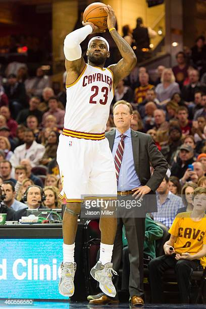 LeBron James of the Cleveland Cavaliers shoots a jump shot as head coach Mike Budenholzer of the Atlanta Hawks watches from the bench during the...