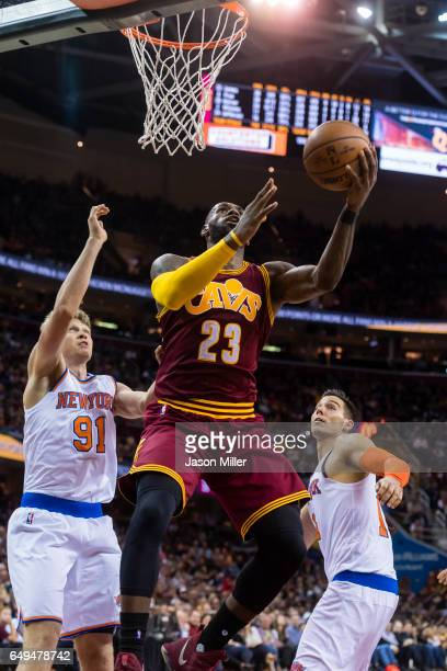 LeBron James of the Cleveland Cavaliers shoots between Mindaugas Kuzminskas and Willy Hernangomez of the New York Knicks during the second half at...