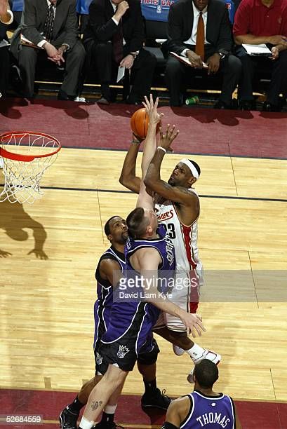LeBron James of the Cleveland Cavaliers shoots over Brad Miller and Cuttino Mobley of the Sacramento Kings during the game at Gund Arena on April 1...