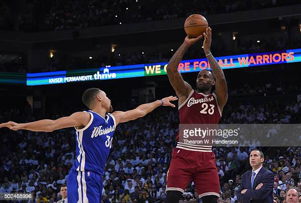 LeBron James of the Cleveland Cavaliers shoots over Stephen Curry of the Golden State Warriors during their NBA basketball game at ORACLE Arena on...